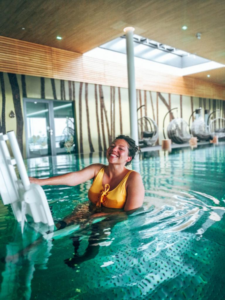 Man sieht Kim von Wheeliewanderlust auf dem Poollift im PanoramaSpa der BioSeehotels in Zeulenroda